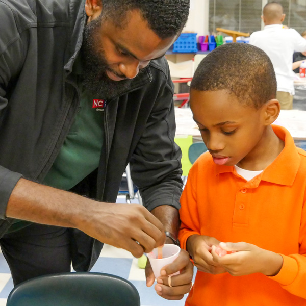 4-H Agent showing an elementary student how to make slime